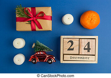 Christmas composition. Calendar with toy car, gift, mandarins, candle on blue trendy background. Festive backdrop for projects. Flat lay style. Top view. Color of the year. December 24