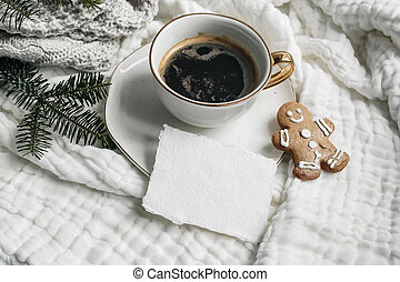 Christmas composition. Cup of coffee, blank cotton card mockup, gingerbread cookie and fir branches on white muslin cotton table cloth, throw. High angle view. Winter holiday lifestyle concept.
