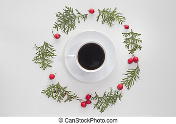 Christmas composition. Cup of coffee with green thuja twigs and red wild rose fruits on white background. Top view, flat lay. Copy space for text