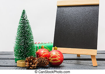 Christmas composition decorations, minimal green fir tree branches with snow and black chalkboard on white background