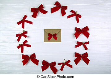 Christmas composition. Envelope in the center of the bows on wooden white background. Flat lay, top view.