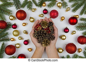 Christmas composition made of golden and red balls for a Christmas tree, cones and fir branches. On white background female hands holding Christmas cones. Winter flat lay