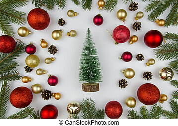 Christmas composition made of golden and red balls for a Christmas tree, fir branches and a decorative christmas tree. in center. Winter flat lay.