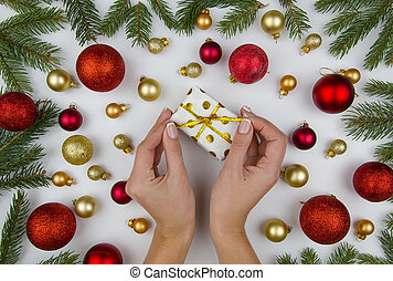 Christmas composition made of golden and red christmas balls, cones and fir branches. On white background female hands holding a small gift box. Winter flat lay