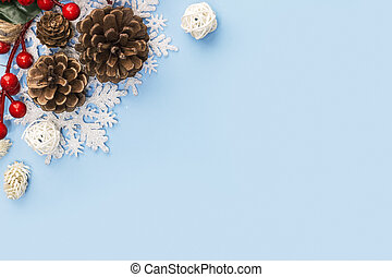 Christmas composition of cones and branches of red berries isolated on a blue background. Christmas, New Year's concept. close-up. Copy space