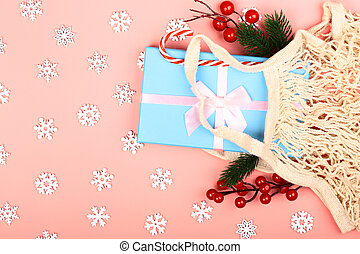 Christmas composition on a pink background. Zero waste. Eco-friendly reusable bag with New Year's gifts. Creative concept. Flat style, top view.