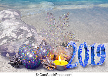 Christmas composition on the sandy seashore and the inscription 2019- New Year card