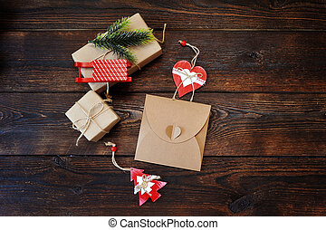 Christmas Composition set of gift kraft boxes with a decor of a fir-tree, sleds and heart on wooden background. Flat lay, top view photo mockup