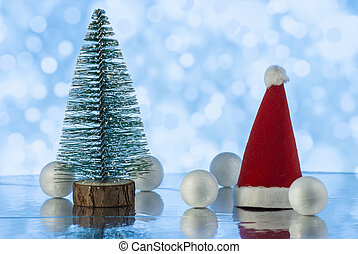 Christmas composition with Christmas tree, Santa claus cap and decorative snowballs against holiday lights background