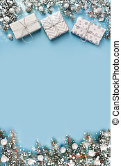 Christmas composition with fir branches tree, white gift boxes on blue background. Merry Xmas card. Winter holiday. Happy New Year. Space for text.