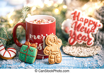 Christmas composition with gingerbread cookies and red cup of hot drink on blurred background.