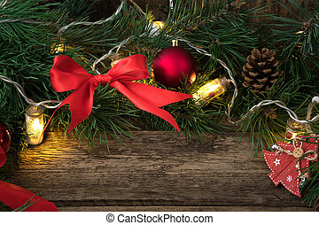 Christmas composition with pine branches, red toys and bows and a burning garland on a natural wooden background.