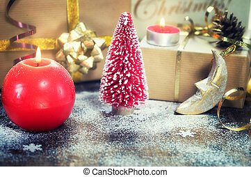 Christmas Composition with present box, red candles, mini xmas tree, festive decorations on wooden background