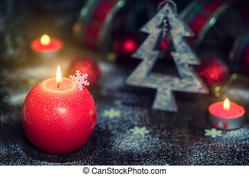 Christmas composition with red candles, festive decorations on old wooden background. Rustic stile