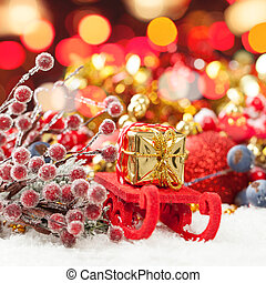 Christmas composition with Santa sleigh, gold gift and colorful Xmas decoration against abstract bokeh light background