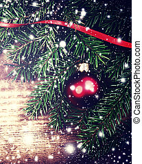 Christmas composition  with Tree Branch,  snowflakes and red bauble . Christmas ornaments with copy space for greeting text, close up.
