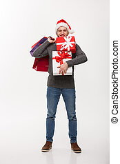 Christmas Concept - attractive young caucasian man enjoy shopping holding a lot of presents in Christmas Day.