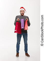 Christmas Concept - attractive young caucasian man surprising shocking gift in shopping bag.