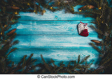Blue wooden table decorated with hearts and light Christmas tree with garlands.