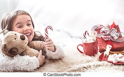 Christmas concept little girl hugging bear toy