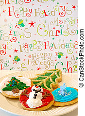 Christmas Cookies - A plate of decorated holiday cookes against a cheerful happy holidays background.