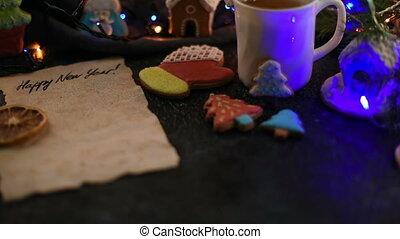 Christmas cookies and cup of tea on daark color bokeh lights...