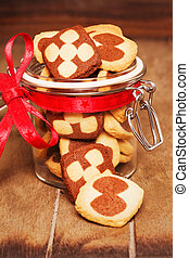 christmas cookies in a jar on wooden background in cozy...