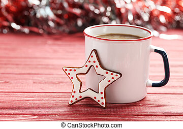 Christmas cookies with cup of hot coffee on a red wooden table
