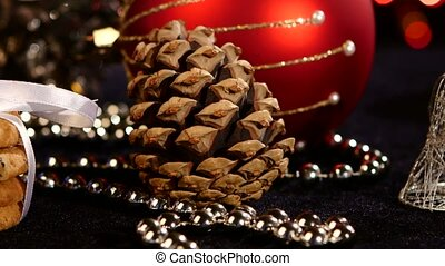 Christmas cookies with decoration, pine cone on black, bokeh, light, garland, cam oves to the left, close up
