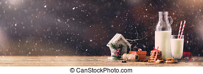Christmas dark background with snow and bokeh, copy space. Banner. Bottle, glass with milk for Santa, cookies, red rope, anise stars, cinnamon sticks, cones, decor on wooden vintage table.