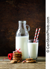 Christmas dark background with snow and bokeh, copy space. Bottle, glass with milk for Santa, cookies, red rope, anise stars, cinnamon sticks, cones, decor on wooden vintage table.