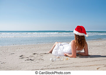 Christmas day at the beach - Woman wiht a santa hat on...