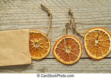 Christmas decor. Dried orange slice in craft paper package on wooden background, top view, minimal flat lay
