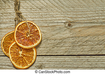 Christmas decor. dried orange slices for new year tree decoration on wooden background, copy space for your text