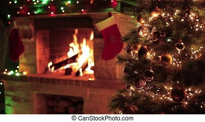 Christmas decorated tree closeup with fireplace interior - ...