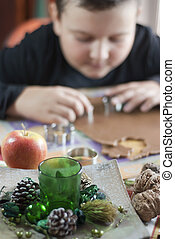Christmas decoration and boy cutting gingerbread dough