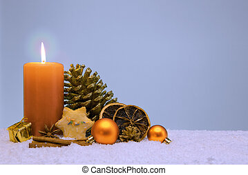 Christmas decoration and yellow advent candle isolated on blue.