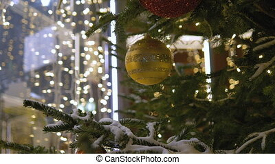 Christmas decoration balls hanging on tree on the background lights garland. Shiny yellow ball.