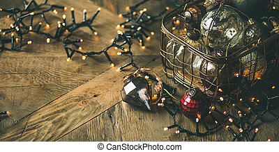 Christmas decoration balls in box and light garland, rustic background