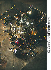 Christmas decoration balls in box and light garland, vertical composition