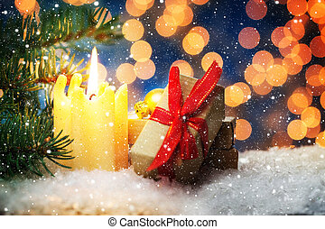Christmas decoration, candle and gifts in the snow