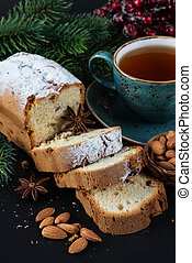 Christmas composition with a cup of tea, sliced cake and spruce branches on a dark background