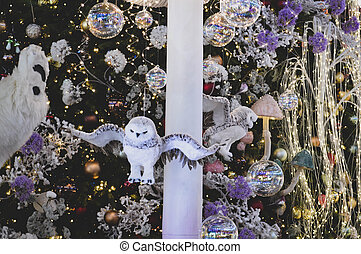 Christmas decoration. Decoration on the Christmas tree in the form of an owl. Surrounded by beads and garland