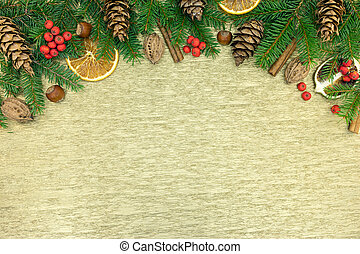 fir-tree branches with spices, cinnamon, nuts, cone, red berries and orange slices