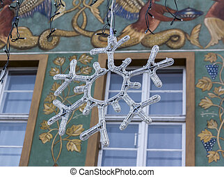 Christmas decoration in the shape of a big snowflake with decorative house facade in background, Poznan, Poland