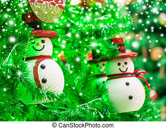 Christmas decoration of snowman on the tree with snow