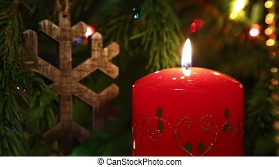 Christmas decoration - candle and wooden snowflake on fir - rack focus