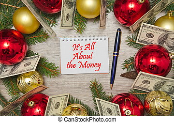 Christmas decoration with dollars and text in notebook IT'S ALL ABOUT THE MONEY on wooden table