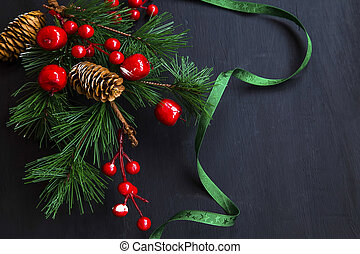 Christmas decoration with fir tree branch with cones, ribbon and red berries
