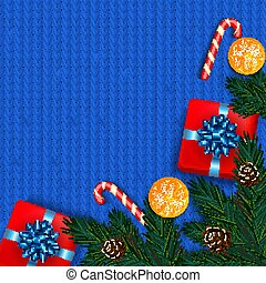 Christmas decoration with fir tree, gift, candy canes on blue kn